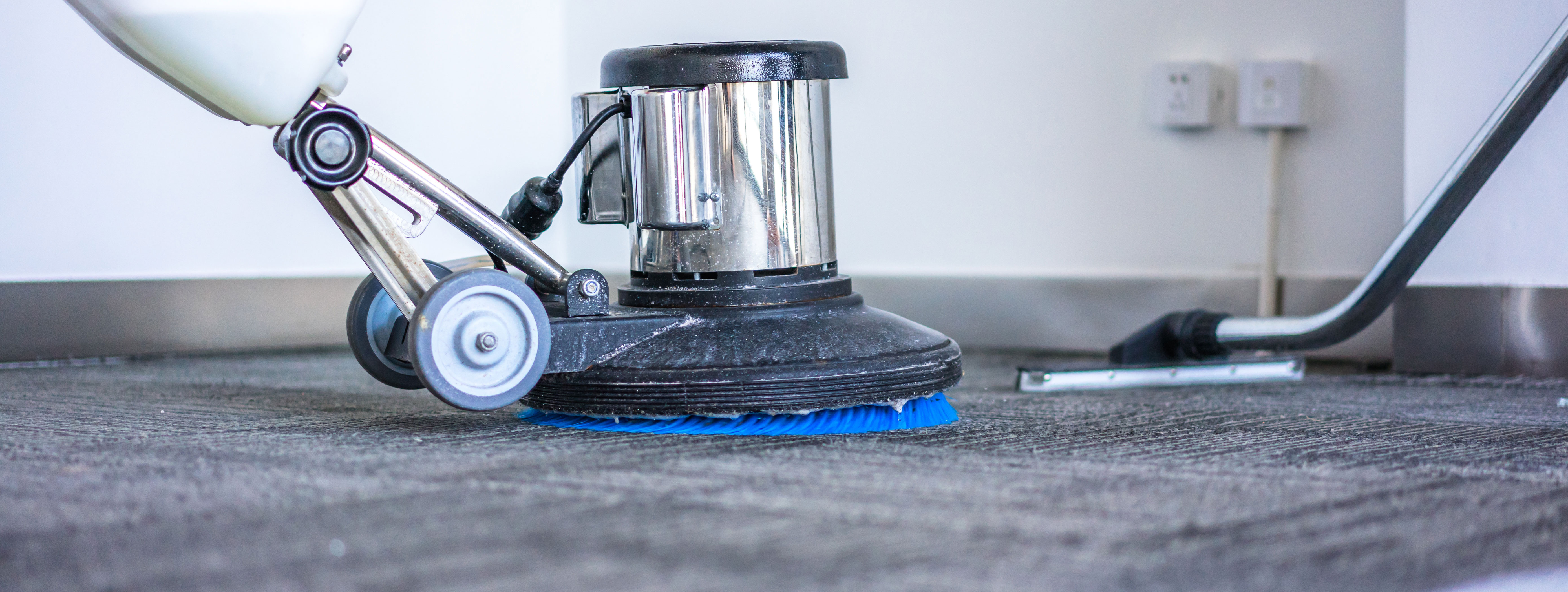 Floor machine cleaning a carpeted floor